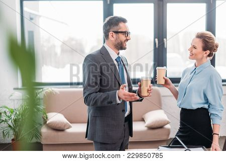 Businesspeople Having Chit-chat While Drinking Coffee At Office