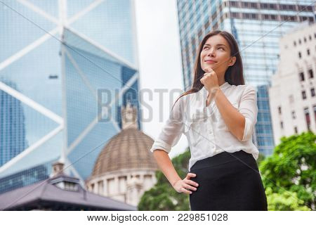 Asian business woman thinking pensive of career goal choice looking up at Hong Kong city, Asia urban lifestyle. Chinese girl holding finger on chin in formalwear office clothing choosing life path.