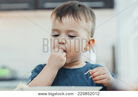 A Beautiful Cheerful Child Eats Pasta With His Hands, Spaghetti All Dirty