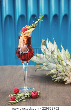 Cocktail Bar Background. Rose Beverage With Liquor, Berries And Vanilla, Decorated With Pineapple Sl