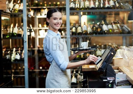 Young cheerful waitress registrating an order and carrying it to the client