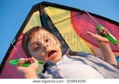 Funny Little Boy With Grimace On His Face Holding Handles Of Color Kite Behind Him
