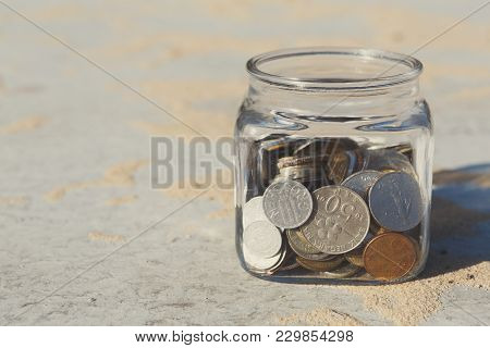 Coins In Glass Jar On Gray Floor With Sand Background, Copy Space. Money Box, Saving Money For Dream