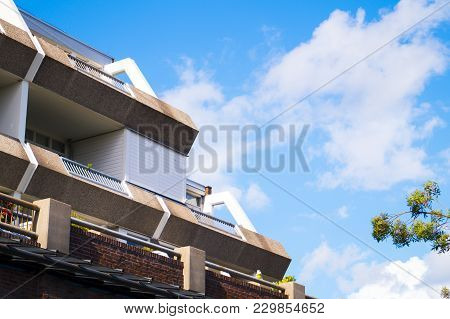 A High Flat Apartment Building With Balconys With Plants And Chairs On Them On A Clear Blue Summer D