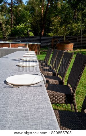Empty Ceramic Round Plates And Cutlery On Grey Tablecloth On Dinner Table In Garden Outdoors, Copy S
