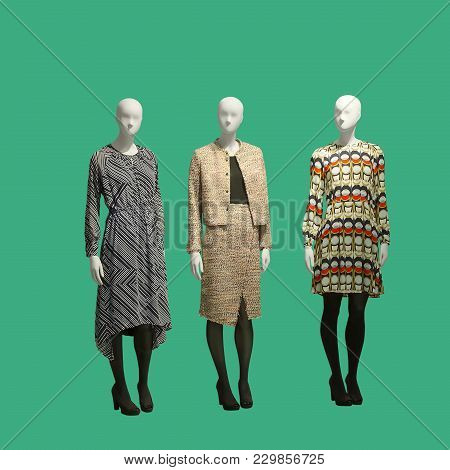 Three Female Mannequins Dressed In Fashionable Clothes Over Green Background. No Brand Names Or Copy