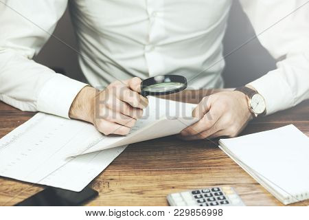 Business Man Reading Documents With Magnifying Glass