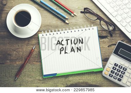 Action Plan Text On Notebook With Keyboard And Stationary On Table