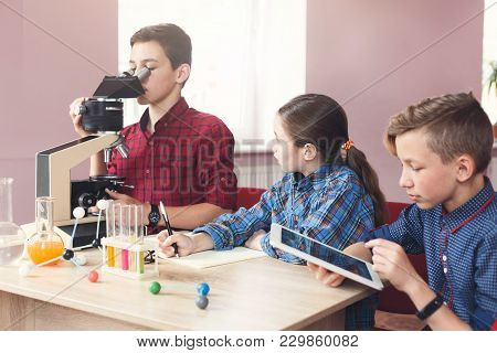 Teenagers Discussing Material At Chemistry Lesson In Laboratory, Sitting With Reagents And Looking I