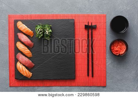 Salmon Sushi On Black Slate Plate. Black Saucer With Soy Sauce, Ginger In Small Bowl, Chopsticks On