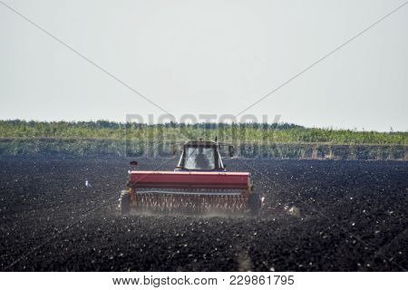 Tractor. Agricultural Machinery Tractor. Tractor With A Seeder In The Field. Sowing Seeds In The Soi