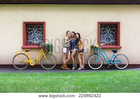 Happy Girls With Bicycles Have Fun. Beautiful Women And Bicycles With Baskets Full Of Wild Flowers.