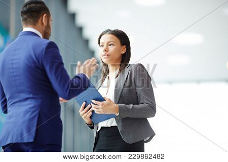 Young businesswoman with document listening to explanation of delegate at meeting