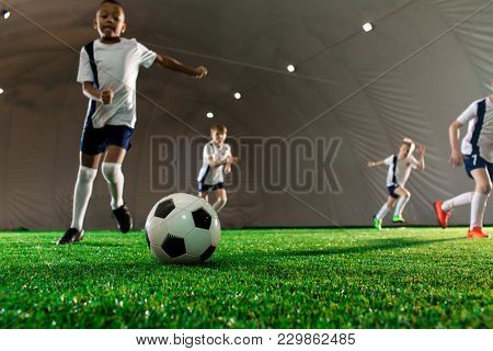 Soccer ball on green pitch and little players running towards it during game