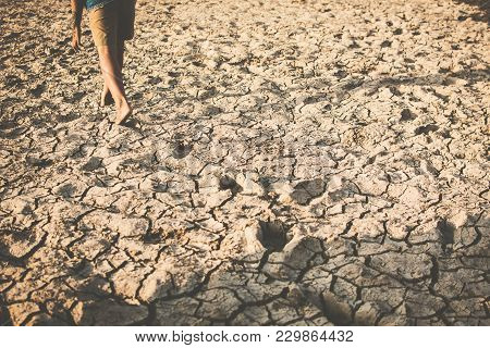 Feet Of Boy Walking On Cracked Dry Ground .concept Hope And Drought