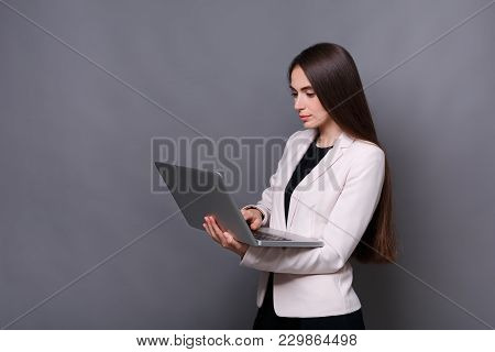 Smart Solutions. Beautiful Thoughtful Business Woman Typing On Laptop While Standing At Gray Studio