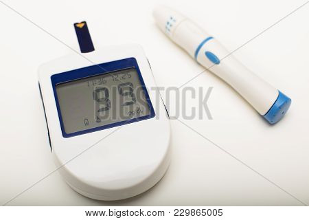 Portable Glucose Meter For Reading Blood Sugar Levels Together With A Lancet For Pricking A Finger T