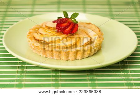 Apple Pie Tart On A Plate With Glaze And A Strawberry