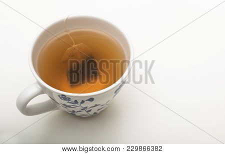 Teabag Steeping In Boiling Water In A Teacup During The Brewing Of A Relaxing Cup Of Tea Over A Whit