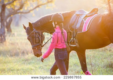 Young Rider Girl Walking With Horse In Park. Equestrian Recreation Activities Background With Copy S