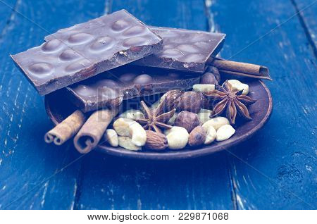 Composition Of Chocolate And Nuts. Blue Toning. Saucer In The Center Of The Frame.