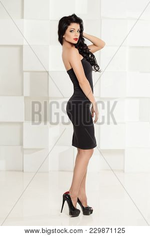 Attractive Brunette Woman Wearing Black Cocktail Dress. Fashion Portrait Of Beautiful Dark Hair Mode