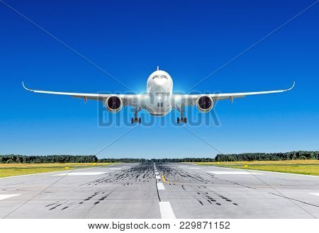 Passenger Airplane With Bright Landing Lights Landing At In Good Clear Weather With A Blue Sky On A
