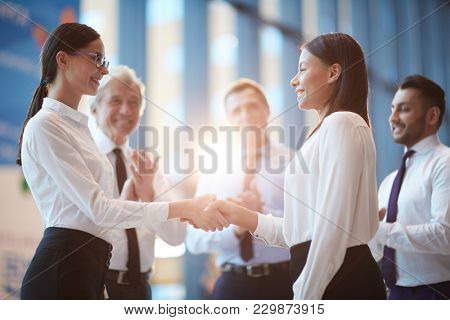 Two young intercultural businesswomen shaking hands and looking at one another with three men applauding near by