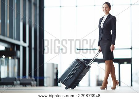 Happy young elegant woman in formalwear pushing suitcase while going to departure platform
