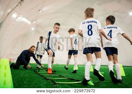 Football team of adorable boys exercising on green pitch on special facilities