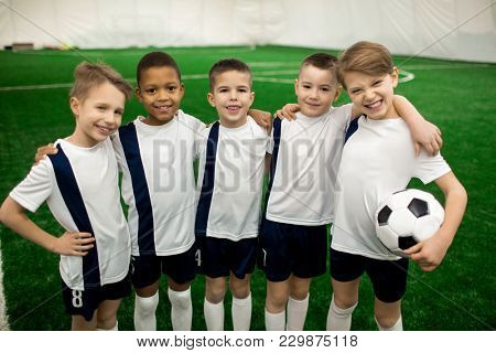 Happy football team of five successful members in uniform looking at camera on pitch
