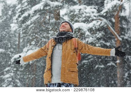 Happy young man with backpack enjoying snowfall while outstretching his arms and closed eyes