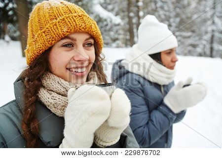 Young smiling female in knitted beanie, scarf and mittens holding hot drink while spending time with friends in winter park