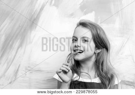 Girl With Blond Hair Eating Red Chilly Pepper On Abstract Colorful Wall. Child And Happy Childhood.