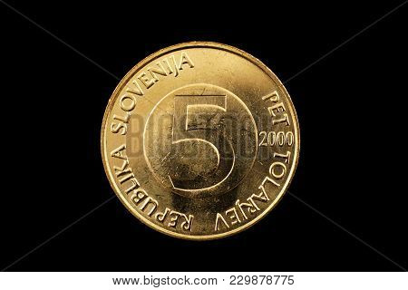 A Macro Image Of A Slovenian Five Tolar Coin Isolated On A Black Background