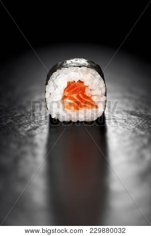 Maki Sushi Roll with Salmon and Rice wrapped in Nori on a black background