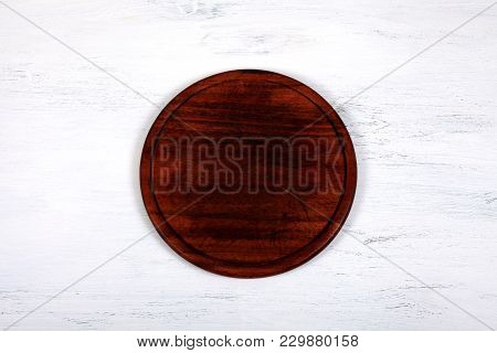 Brown Wood Cutting Board On White Wooden Kitchen Table. Empty Round Cutting Board For Cutting Bread,