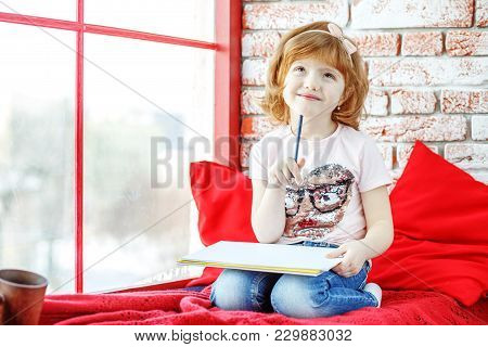 Beautiful Kid Fantasizes And Paints On The Windowsill. The Concept Is Childhood, Learning, Drawing,