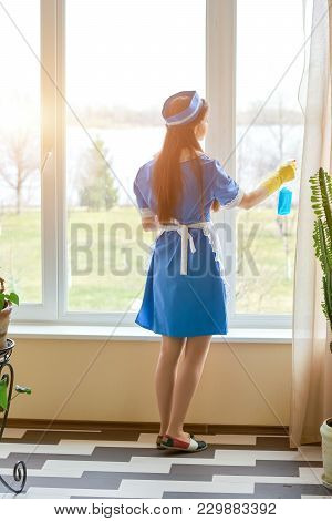 Housemaid Cleaning A Window. Woman Holding Detergent Bottle.