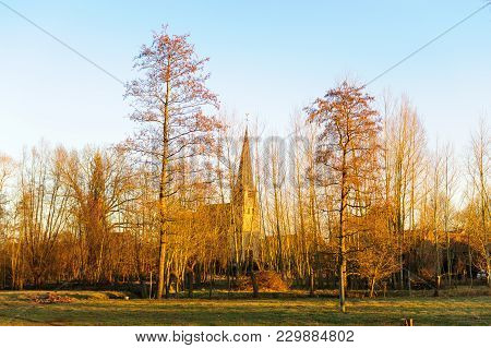 A Church From A Flemish Village In The Belgian Country Side Is Casting Long Shadows On A Clear Winte