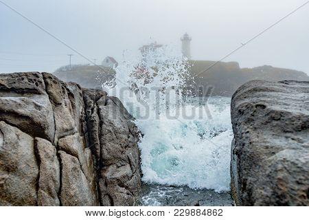 Wave Crashes On Rocks At Cape Neddick Lighthouse Along Maine Coast