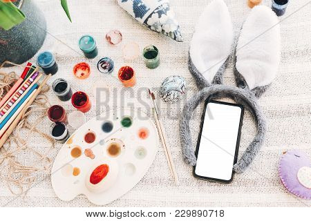 Bunny Ears And Phone With Empty Screen Ang Egg And Colorful Paint On Rustic Background Flat Lay. Spa