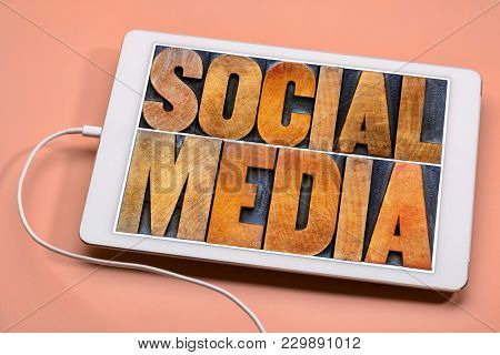 social media word abstract in antique wood letterpress printing blocks on a screen of a digital tablet