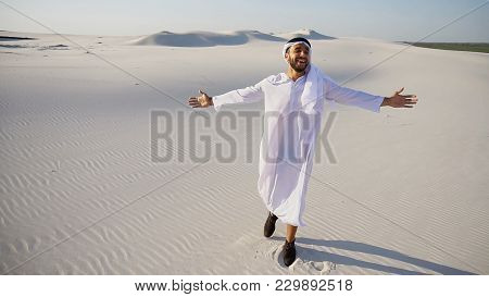 Handsome Young Emirate Arabian Uae Sheikh Strolls And Looks Around Wide Desert With White Sand. Musl