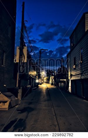 Dark city alley during sunset with dramatic sky and clouds
