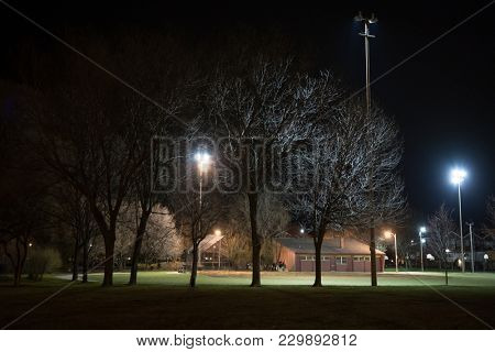 City park with a baseball field and building at night