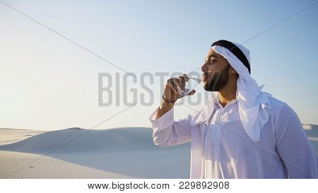 Stately Arab Young Man Quenches Thirst With Glass Of Cool Water And Feels Influx Of Strength And Ene