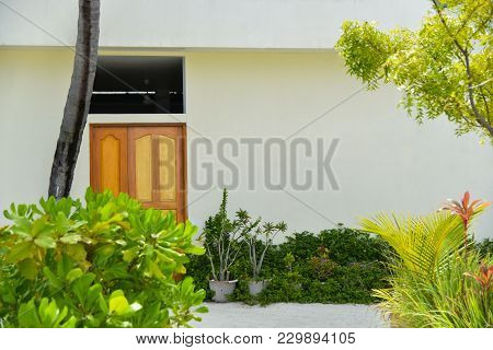 Charming Small Home With Brown Front Door And Summer Garden Containers Filled With Annual Flowers.