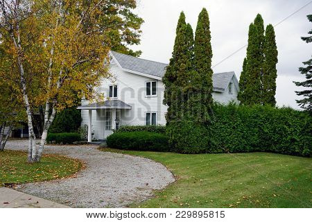Bay View, Michigan / United States - October 16, 2017: A White Two Story Cottage, With A Gravel Driv
