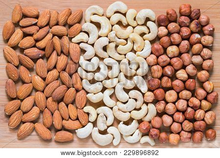 Almond, Cashew And Hazel Nut On Light Wooden Background. Nut Kernel Texture. Organic Food Banner Tem